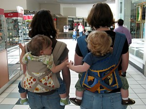 Two women wearing their babies while walking through the mall