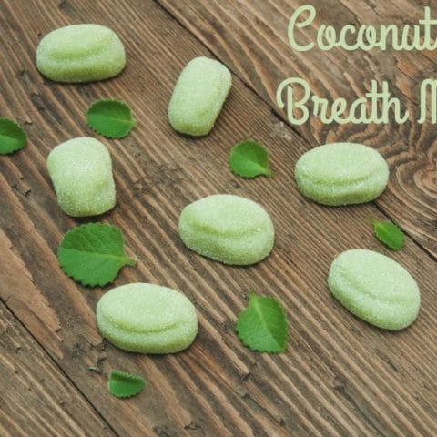 DIY homemade coconut oil breath mints on a wooden background with mint leaves