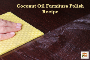 Someone using a yellow cloth with coconut oil furniture polish on a dark desktop