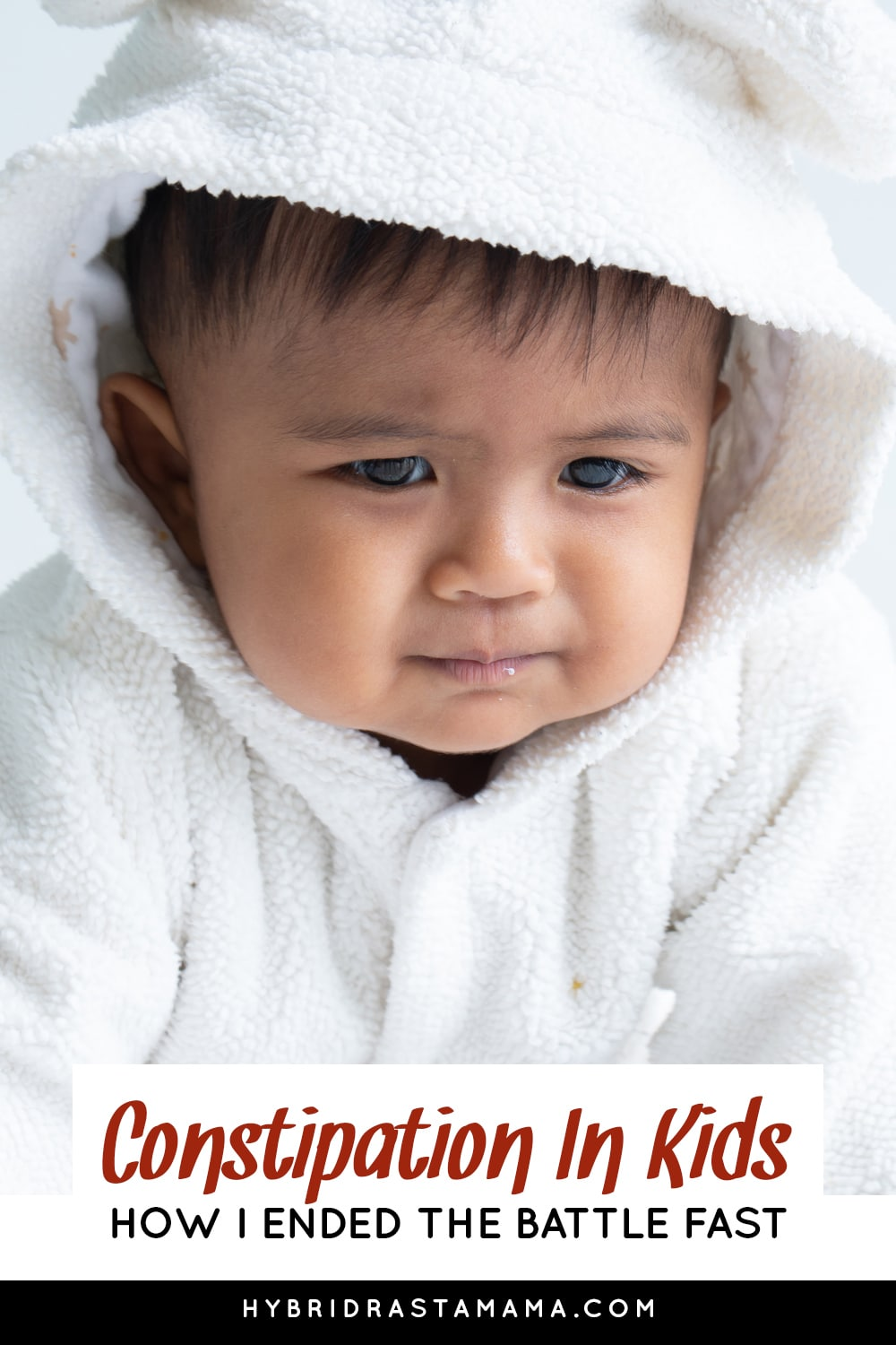 A constipated child in a white robe with a hood looking miserable.