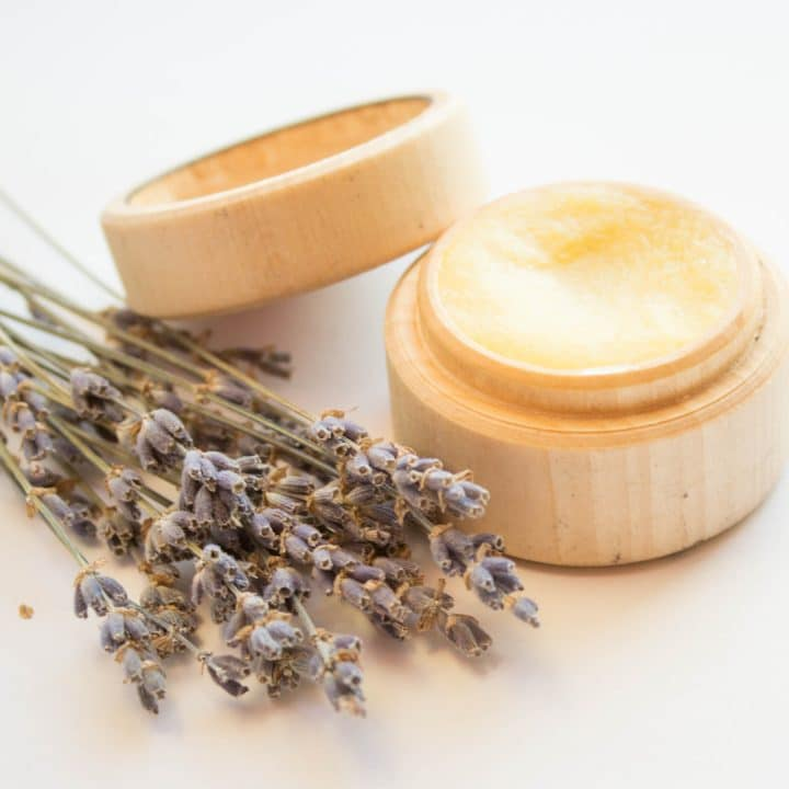 DIY hand cream to repair overwashed hands in a small wooden container with a sprig of lavender next to it