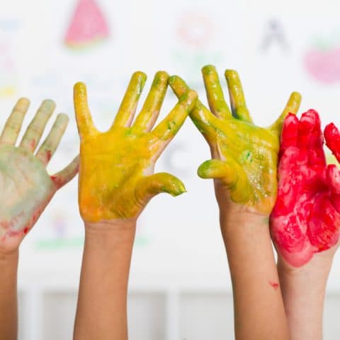 kids hands covered with DIY whipped cream finger paint