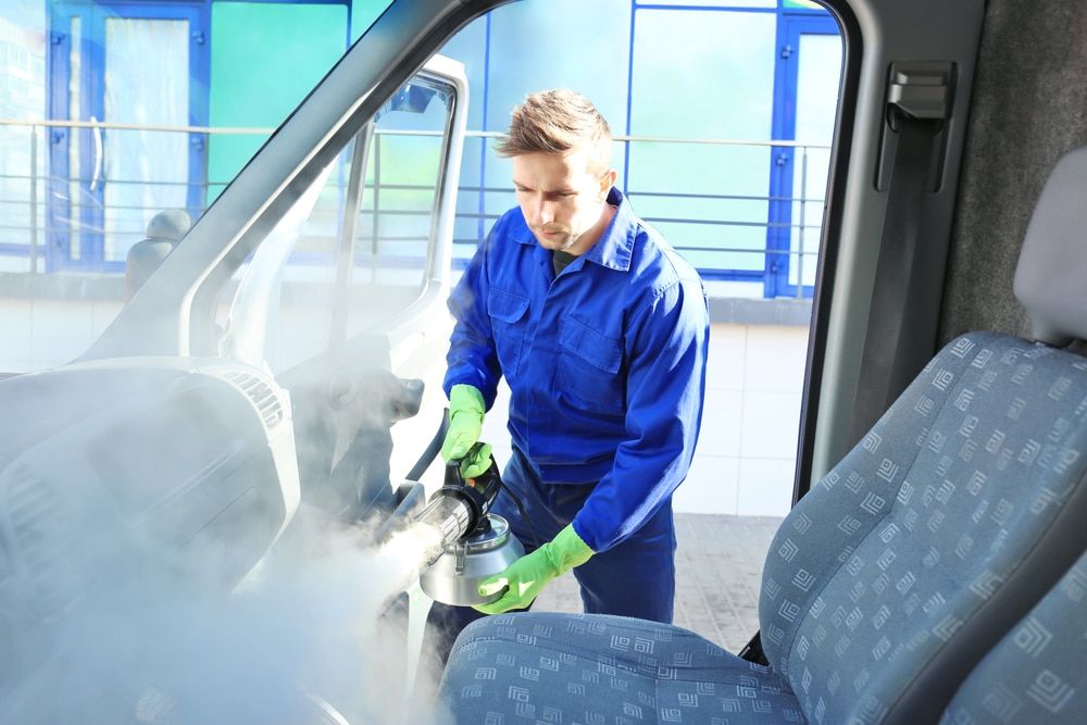 A young man in blue coveralls fogging the inside of a car with blue seats. He is trying to remove mold in cars.