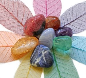 A collage of crystals to support chakras on a leaf background