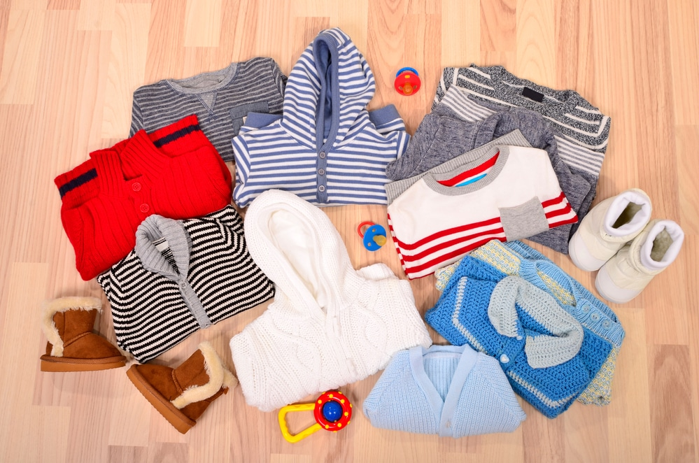 Baby clothes lying on the floor. Winter child sweaters arranged, colorful wardrobe for toddler.