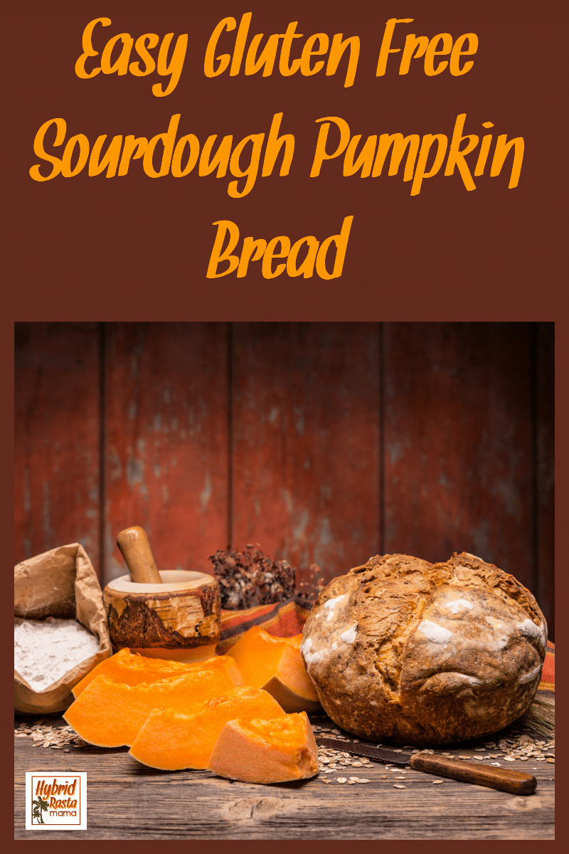 Gluten free sourdough bread on a wood cuting board surrounded by slices of fresh pumpkin