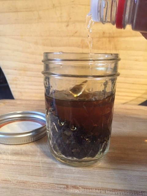 Elderberry elixir in mason jar ready to be stirred