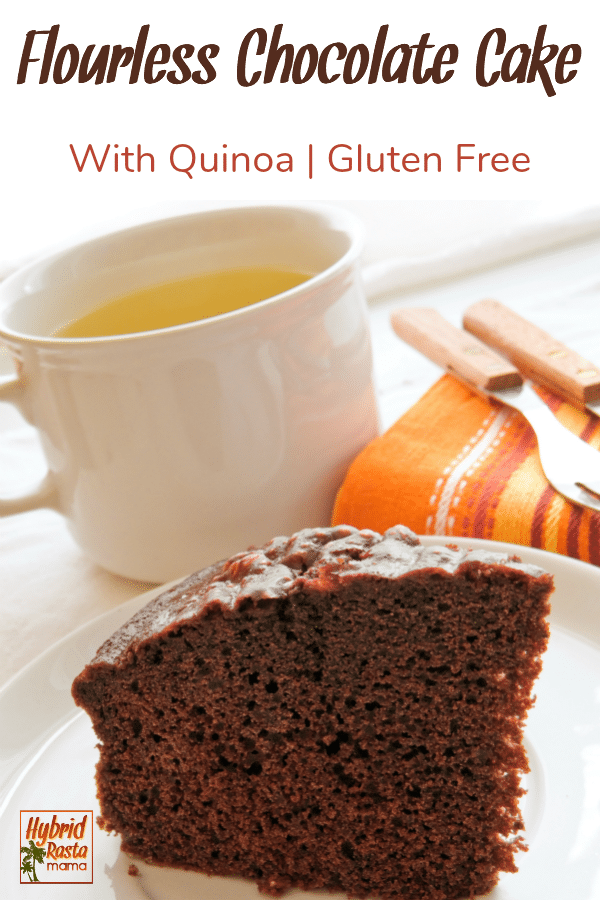 A slice of flourless chocolate cake with quinoa on a white plate with a cup of steaming tea