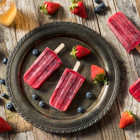 Homemade berry kombucha popsicles on a fancy brown platter surrounded by berries
