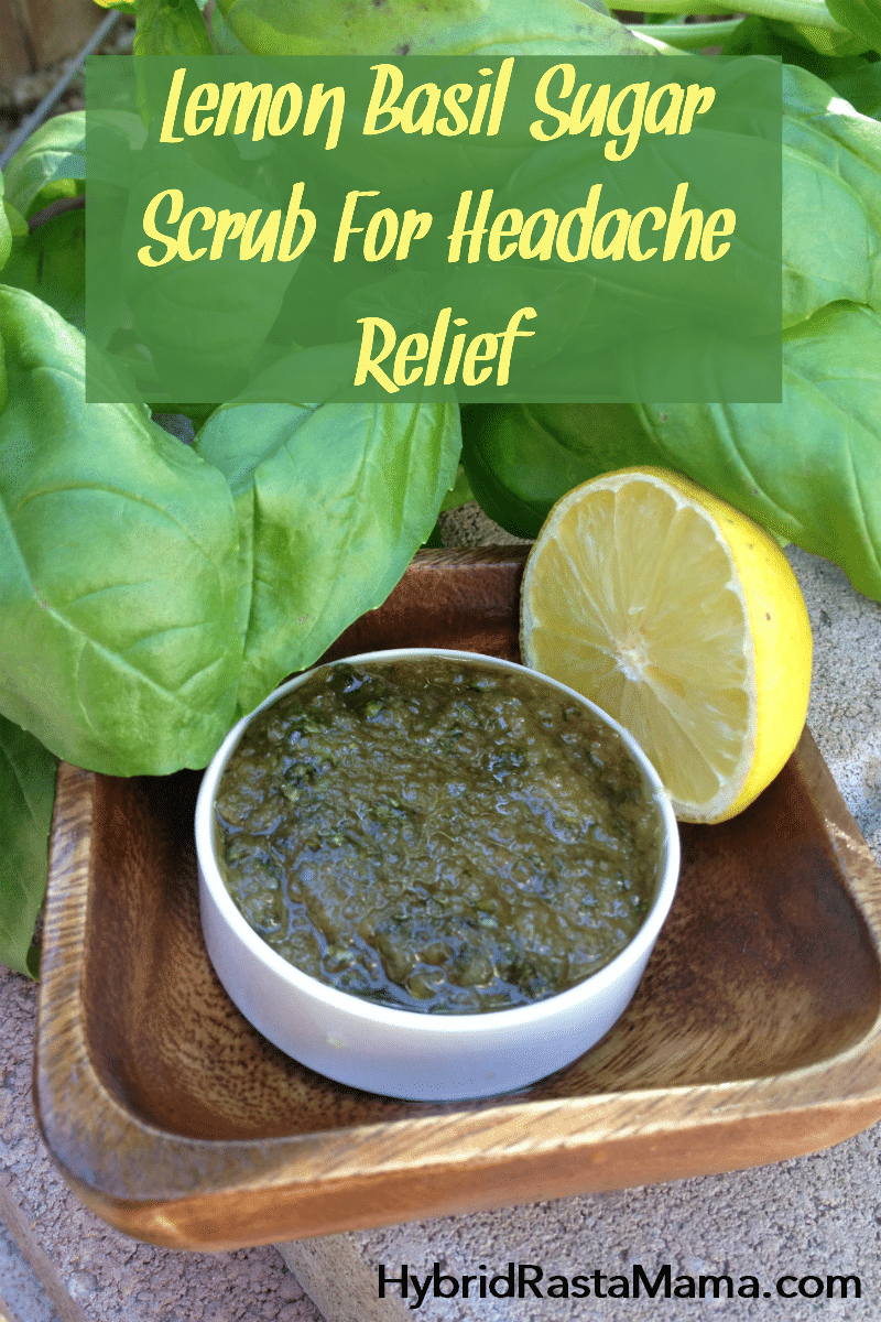 A white glass bowl of lemon basil sugar scrub for headache relief. It is surrounded by fresh basil and a cut lemon