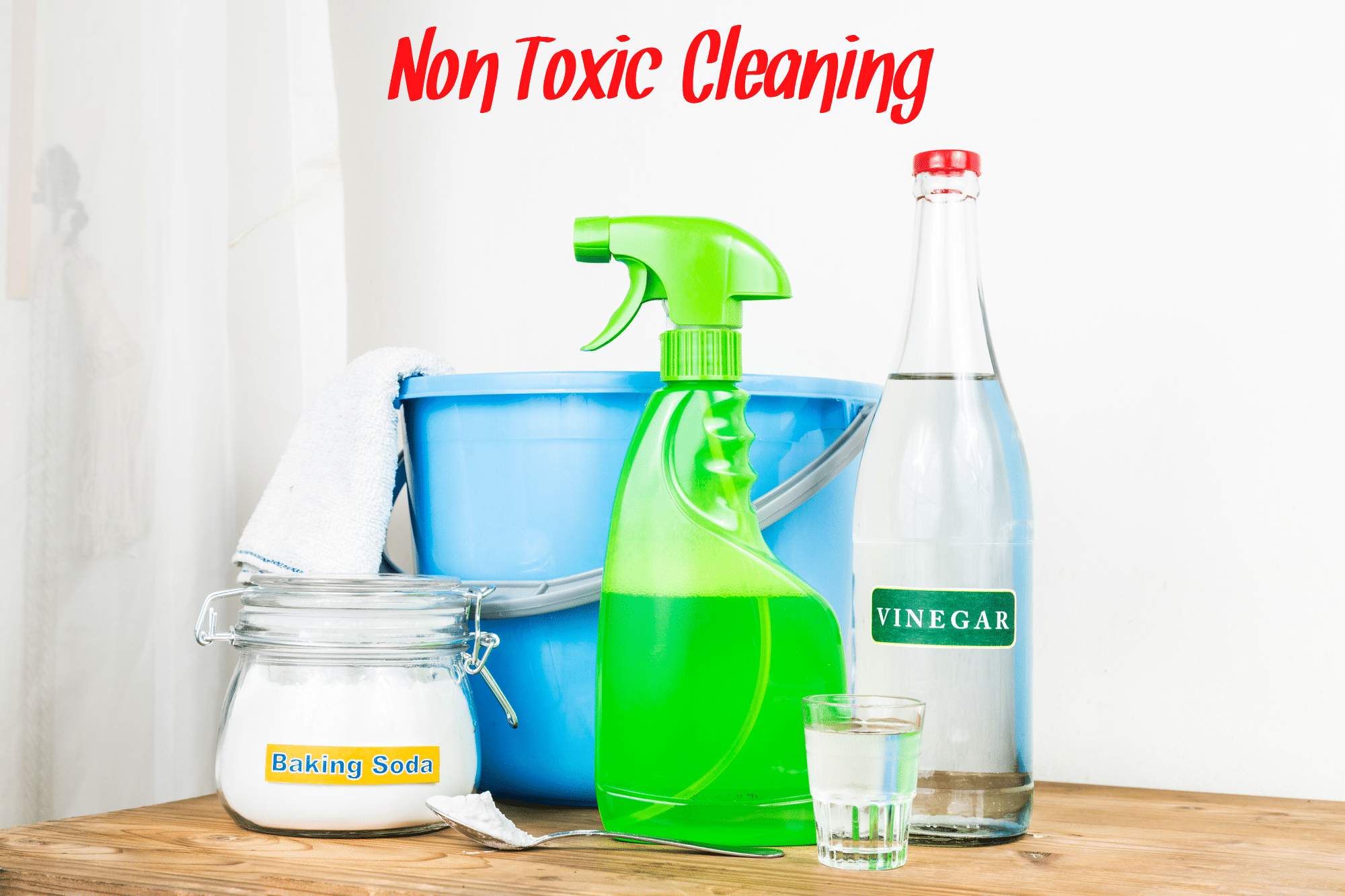 A blue plastic bucket, a bottle of white vinegar, a jar of baking soda, a green spray bottle, and a measuring cup. All part of non toxic cleaning recipes.