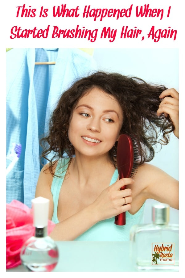 A brunette wavy hair woman brushing her her with a boar bristle brush while looking in the mirror.