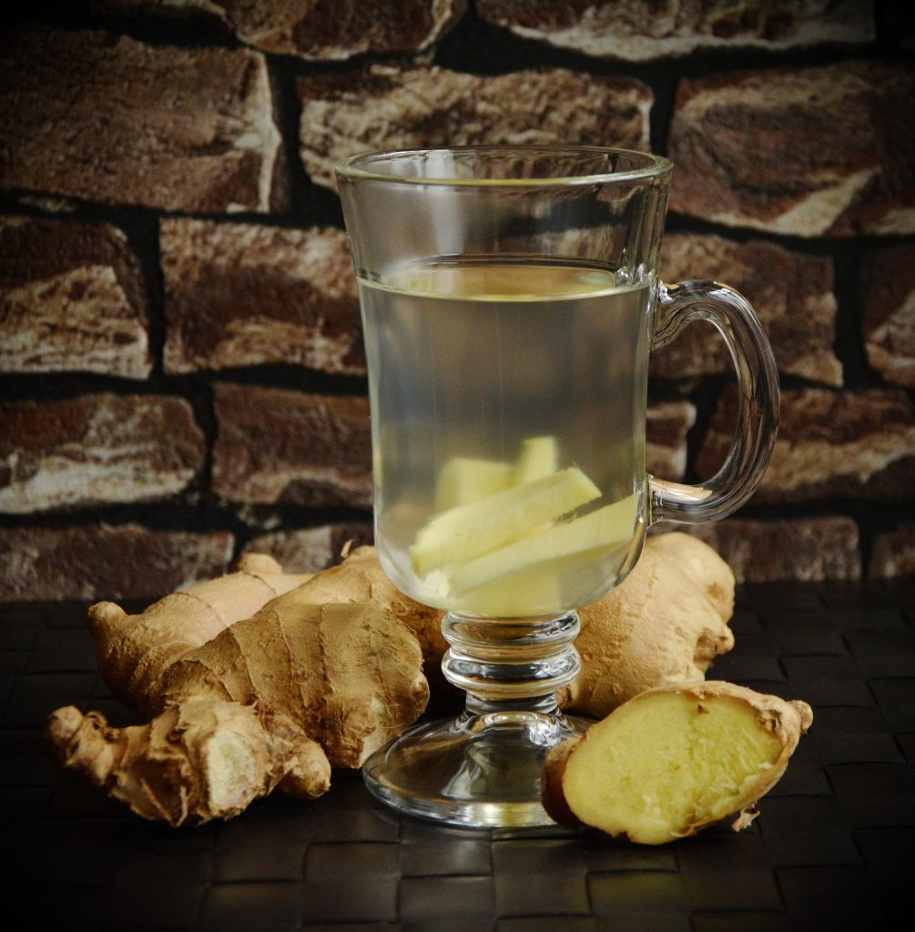 A glass of warm water with ginger root in it surrounded by chunks of ginger against a brown brick background